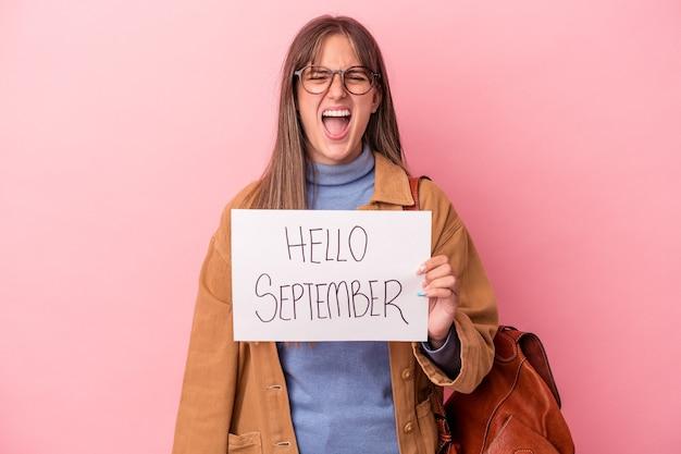 非常に怒って攻撃的な叫び声ピンクの背景に分離されたこんにちは9月のプラカードを保持している若い白人学生の女性。