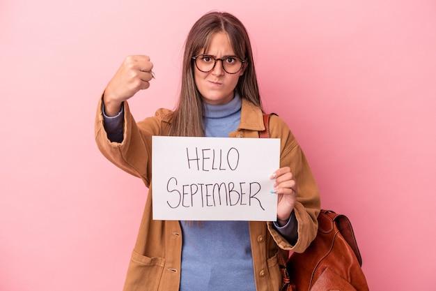 カメラに拳、攻撃的な表情を示すピンクの背景に分離されたこんにちは9月のプラカードを保持している若い白人学生の女性。