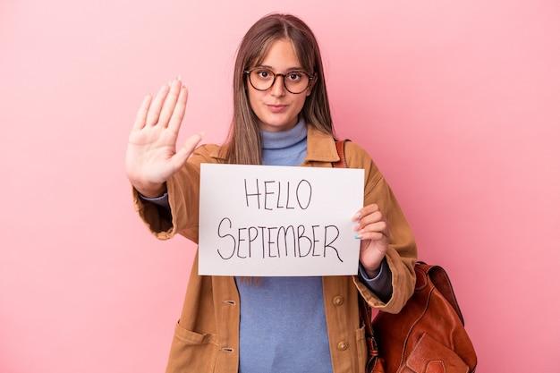 一時停止の標識を示す伸ばした手で立っているピンクの背景に分離されたこんにちは9月のプラカードを保持している若い白人学生の女性は、あなたを防ぎます。