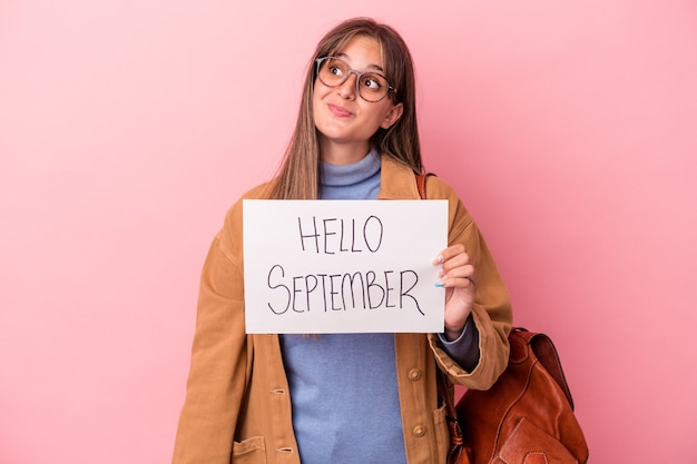 Young caucasian student woman holding hello september placard isolated on pink background dreaming of achieving goals and purposes