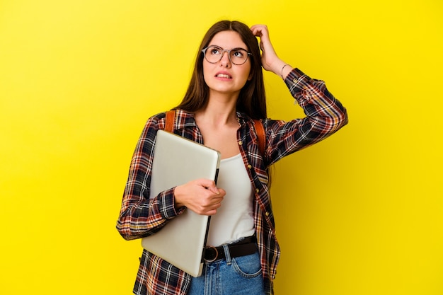 Young caucasian student woman holding a laptop isolated on pink background being shocked, she has remembered important meeting.