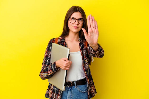 Young caucasian student woman holding a laptop isolated on pink background standing with outstretched hand showing stop sign, preventing you.