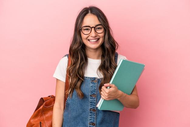 ピンクの背景に分離された若い白人学生女性幸せ、笑顔、陽気な。