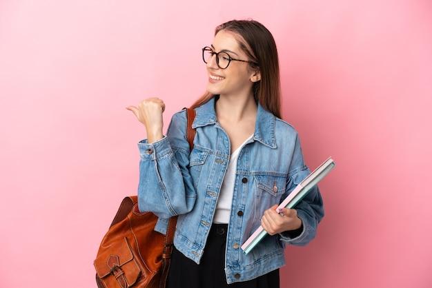 製品を提示する側を指しているピンクで隔離の若い白人学生女性