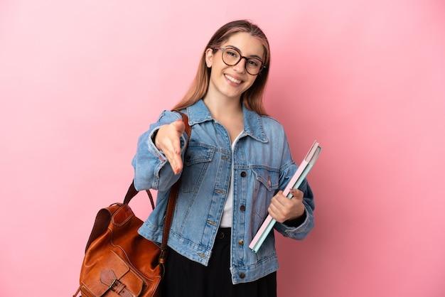 Молодая кавказская студентка изолирована на розовой стене, пожимая руку для заключения хорошей сделки