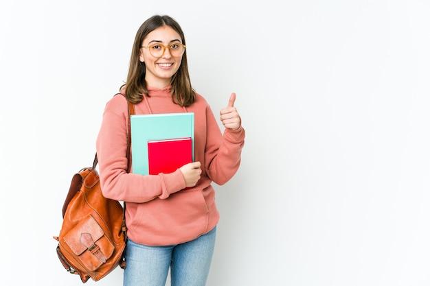 Молодая кавказская студентка изолирована на белой стене, улыбаясь и поднимая палец вверх