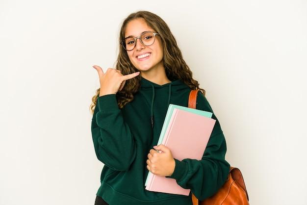 Молодая кавказская женщина студента изолировала показывая жест звонка мобильного телефона с пальцами.