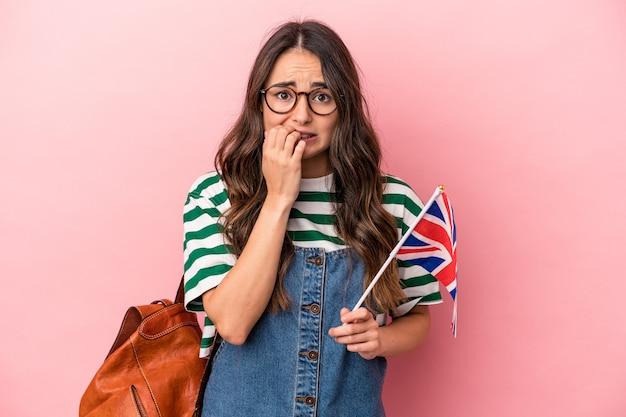 神経質で非常に不安なピンクの背景に爪を噛んで孤立した英語を勉強している若い白人学生の女性。