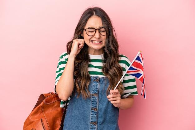 手で耳を覆うピンクの背景に分離された英語を勉強している若い白人学生の女性。