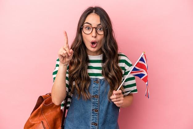 アイデア、インスピレーションの概念を持つピンクの背景に分離された英語を勉強している若い白人学生の女性。