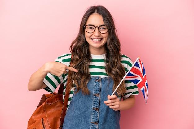 誇りと自信を持って、シャツのコピースペースを手で指しているピンクの背景の人に分離された英語を勉強している若い白人学生女性