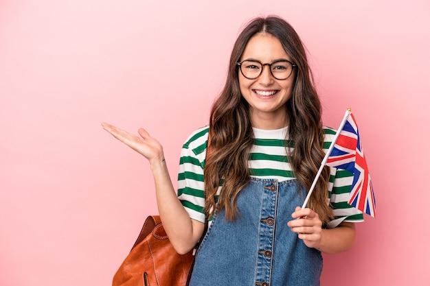 ピンクの背景に分離された英語を勉強している若い白人学生の女性は、手のひらにコピースペースを示し、腰に別の手を保持しています。