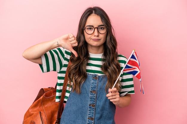 嫌いなジェスチャーを示すピンクの背景に分離された英語を勉強している若い白人学生の女性は、親指を下に向けます。不一致の概念。