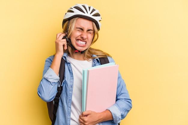 手で耳を覆う黄色の背景に分離された自転車のヘルメットを身に着けている若い白人学生の女性。