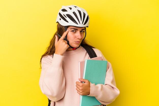黄色の背景に分離された自転車のヘルメットを身に着けている若い白人学生の女性は、指で寺院を指して、考えて、タスクに焦点を当てた。
