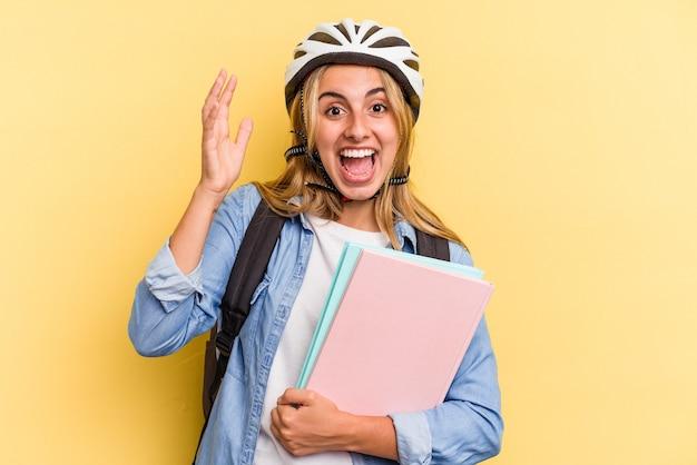 黄色の背景に分離された自転車のヘルメットを身に着けている若い白人学生の女性は、嬉しい驚きを受け取り、興奮し、手を上げます。