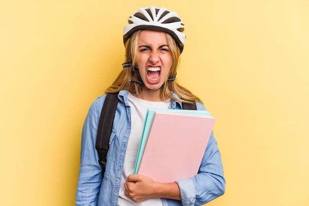 非常に怒って攻撃的な叫び声黄色の背景に分離された自転車のヘルメットを身に着けている若い白人学生の女性。