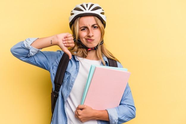 嫌いなジェスチャーを示す黄色の背景に分離された自転車のヘルメットを身に着けている若い白人学生の女性は、親指を下に向けます。不一致の概念。