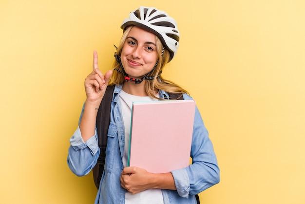 指でナンバーワンを示す黄色の背景に分離された自転車のヘルメットを身に着けている若い白人学生の女性。