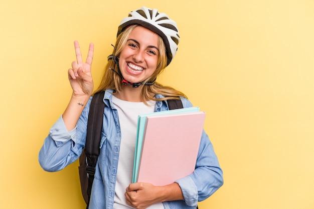 指で2番目を示す黄色の背景に分離された自転車のヘルメットを身に着けている若い白人学生の女性。