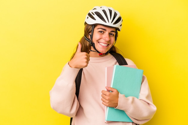 笑顔と親指を上げて黄色の背景に分離された自転車のヘルメットを身に着けている若い白人学生女性