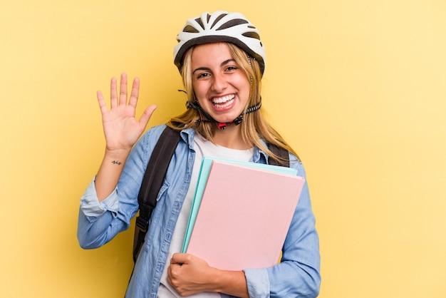 黄色の背景に分離された自転車のヘルメットを身に着けている若い白人学生の女性は、指で5番を示して陽気に笑っています。