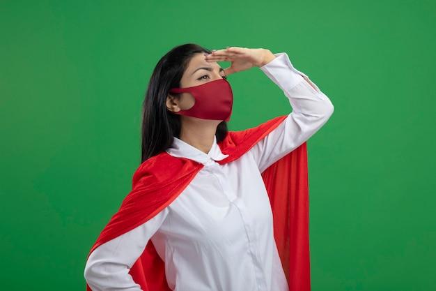 Giovane ragazza caucasica del supereroe in piedi in vista di profilo mettendo la mano sulla testa guardando dritto in parete verde isolata distanza con lo spazio della copia