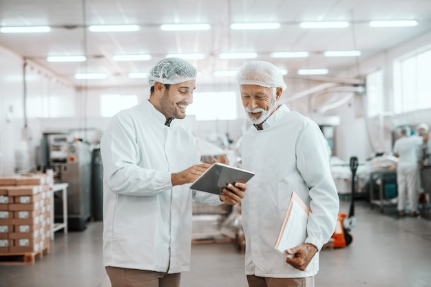 Young caucasian supervisor showing results of food quality on tablet to his older colleague. senior man holding folder with charts. both are dressed in uniforms and having hairnets. food plant.