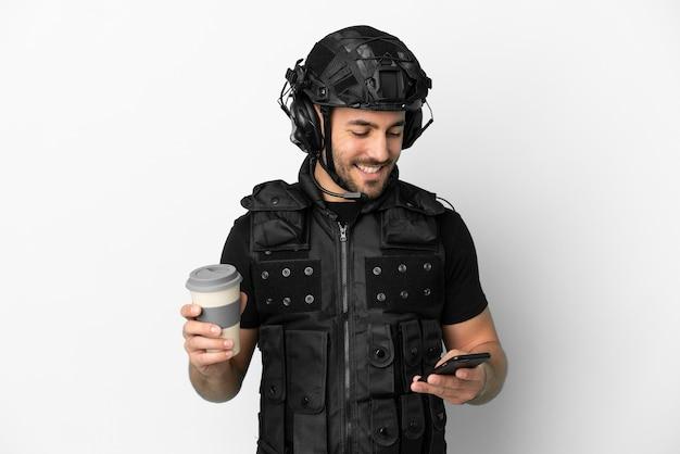Молодой кавказский спецназ на белом фоне держит кофе на вынос и мобильный