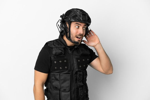 Молодой кавказский спецназ изолирован на белом фоне, слушая что-то, положив руку на ухо