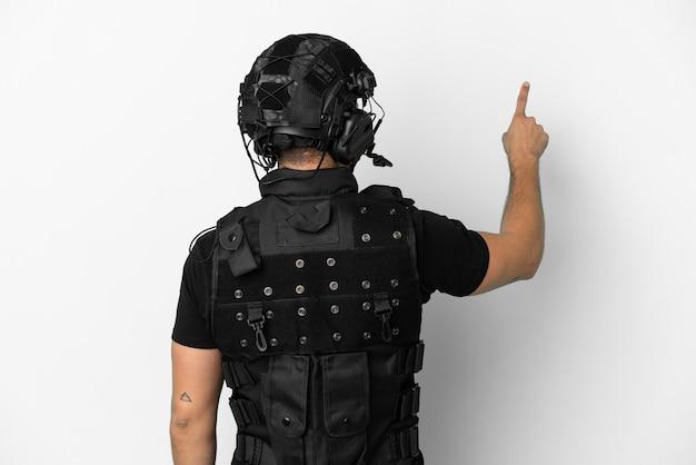 Молодой кавказский спецназ изолирован на белом фоне, указывая указательным пальцем назад