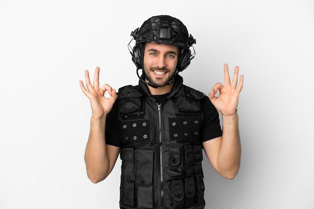 Молодой кавказский спецназ изолирован на белом фоне, показывая пальцами знак ок