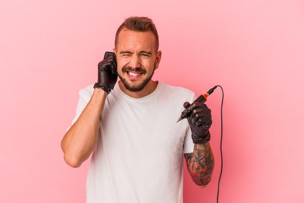 手で耳を覆うピンクの背景に分離された若い白人のタトゥーアーティスト。