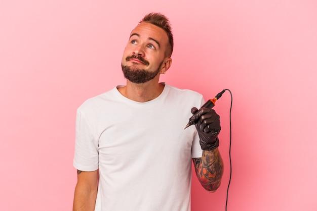 目標と目的を達成することを夢見ているピンクの背景に分離された若い白人のタトゥーアーティスト