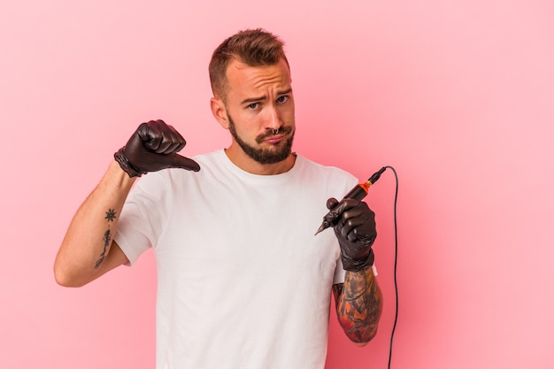 Young caucasian tattoo artist isolated on pink background  feels proud and self confident, example to follow.