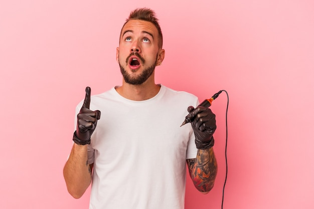 Young caucasian tattoo artist isolated on pink background  pointing upside with opened mouth.