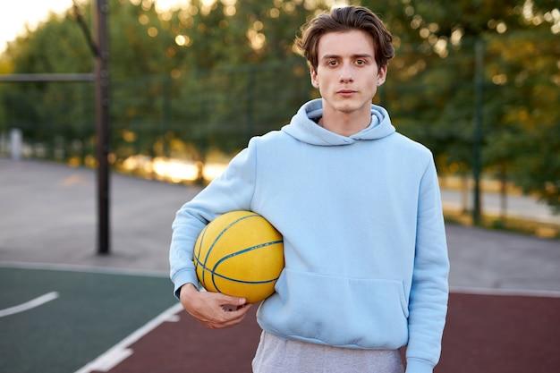 Молодой кавказский подросток мальчик играет в баскетбол