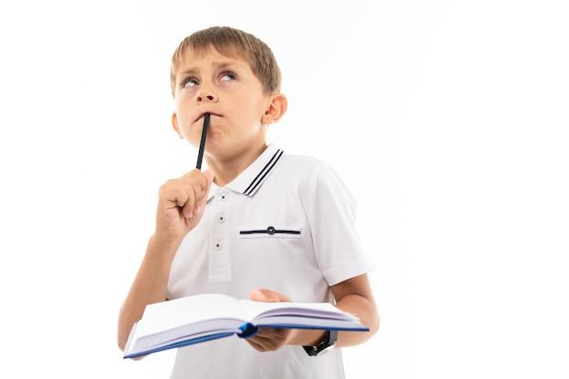 若い白人のティーンエイジャーは宿題をし、白で隔離されると考えています