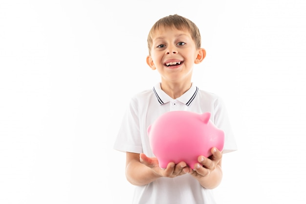 Young caucasian teenager holds a pink pig moneybox on white