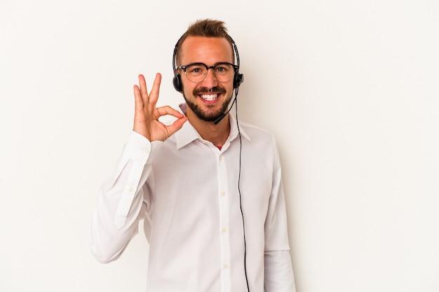 白い背景に分離された入れ墨を持つ若い白人のテレマーケターの男は、陽気で自信を持って大丈夫なジェスチャーを示しています。