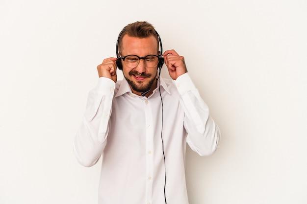 手で耳を覆う白い背景で隔離の入れ墨を持つ若い白人のテレマーケターの男。