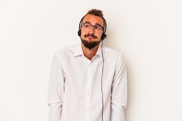 目標と目的を達成することを夢見ている白い背景で隔離の入れ墨を持つ若い白人テレマーケター男