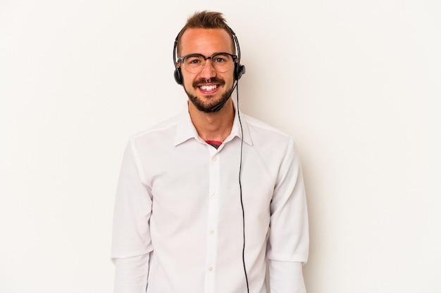 白い背景に分離された入れ墨を持つ若い白人のテレマーケターの男は幸せ、笑顔、陽気な。