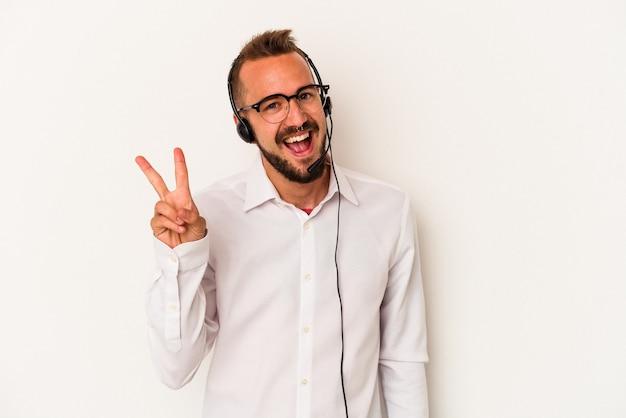 白い背景に隔離された入れ墨を持つ若い白人のテレマーケターの男は、指で平和のシンボルを喜んで気楽に示しています。