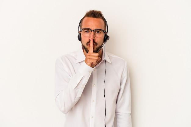 秘密を保持するか、沈黙を求めて白い背景で隔離の入れ墨を持つ若い白人のテレマーケターの男。