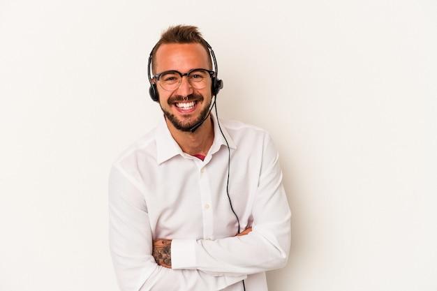 笑って楽しんでいる白い背景に分離された入れ墨を持つ若い白人のテレマーケターの男。