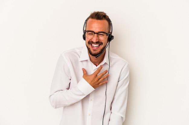 白い背景に分離された入れ墨を持つ若い白人のテレマーケターの男は、胸に手を置いて大声で笑います。