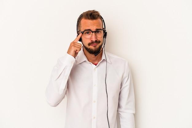 指で寺院を指して、思考、タスクに焦点を当て、白い背景に分離された入れ墨を持つ若い白人のテレマーケターの男。