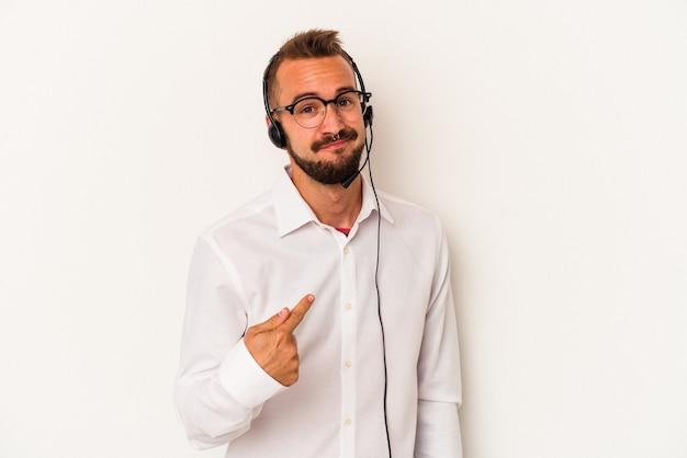 誘うようにあなたに指で指している白い背景に分離された入れ墨を持つ若い白人のテレマーケターの男が近づいています。