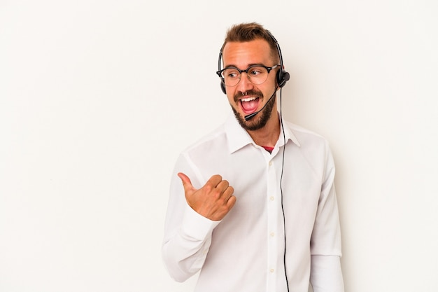 白い背景に隔離された入れ墨を持つ若い白人のテレマーケターの男は、親指の指を離れて、笑って気楽にポイントします。
